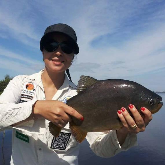 pescadora com pacu fisgado na pescaria no pantanal